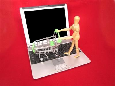 パソコンの上で買い物をする人形
